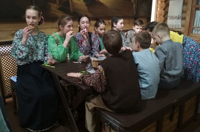 Деревенские ребятишки сидят за столом.