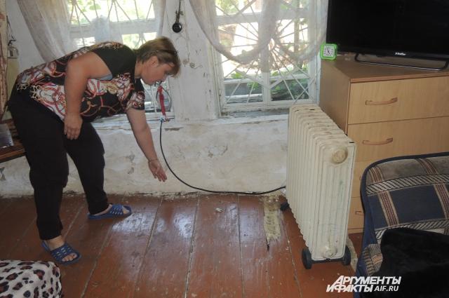 Елена показывает, насколько сильно провалился пол в ее доме.