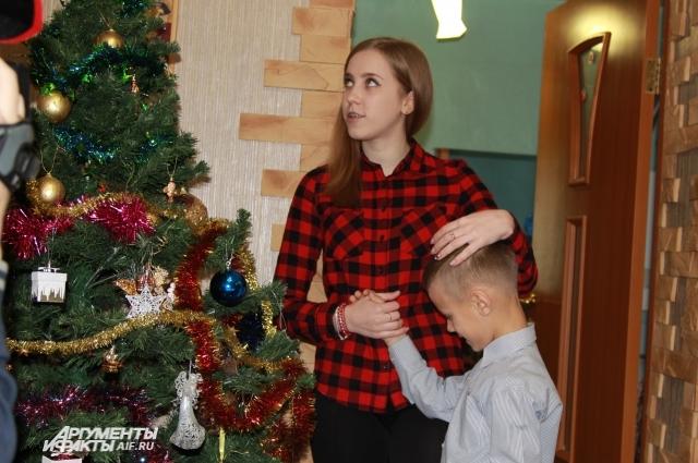 Семён показывает сестре ёлку, которую он нарядил с приёмной мамой.