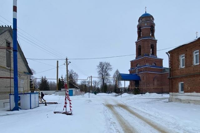 Справа из красного кирпича и слева из белого стоят два здания школы, рядом расположен храм, за которым виднеется кладбище.