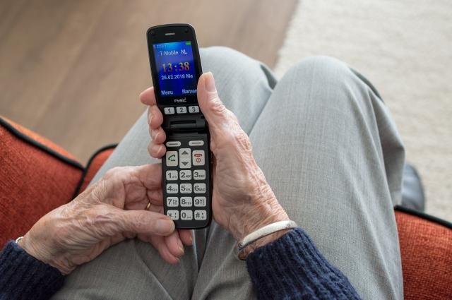 Пенсионер с мобильным телефоном.