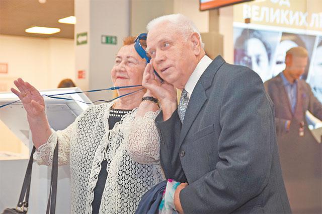 Москвичка Лидия Мельникова с супругом Игорем Бородиным  на выставке в МФЦ, где представлены письма и портрет её отца.