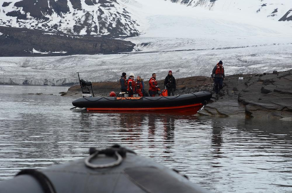 С корабля на берег члены команды плыли на надувных лодках.