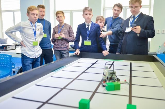 Роботы, запрограммированные юными технарями, шустро бегают по столам, собирая кубики.