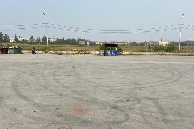 Асфальт на остановке автобусов возле Медцентра полностью в следах от шин.