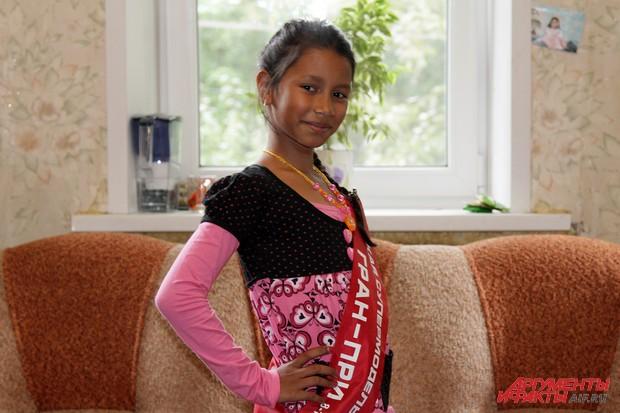 Лиза, надев ленту, выданную за победу в общероссийском конкурсе красоты, сразу принимает позу для фотосессии, лицо сияет улыбкой