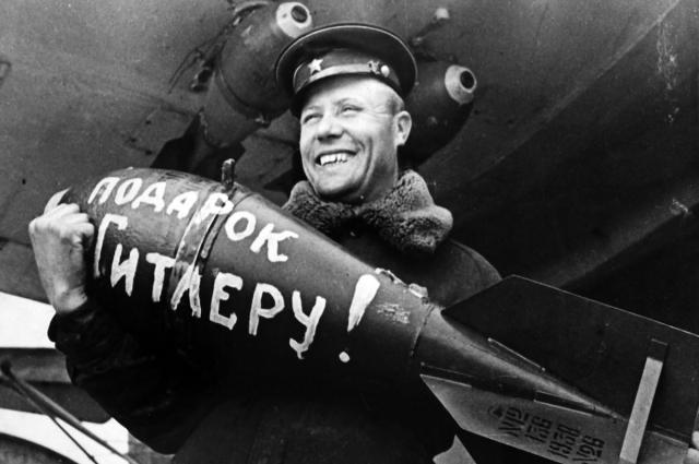 Оружейник авиачасти морской авиации Черноморского флота сержант П.М. Корнейко с авиабомбой в руках, готовит самолет к боевому вылету. Авторское название фото - «Подарок Гитлеру».