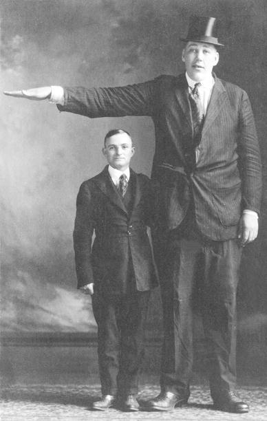 Фотография актера Джона Осена, стоящего рядом с мужчиной нормального роста.