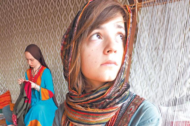 Девушки втрадиционных афганских нарядах ткут изшерсти.