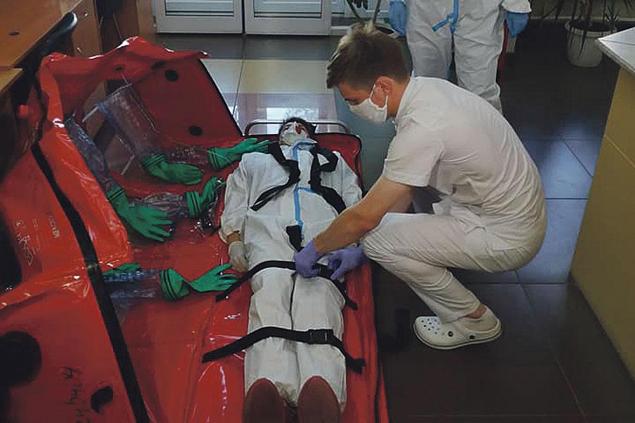 Медработники скорой помощи тренируются перевозить больных коронавирусом с помощью специального бокса.