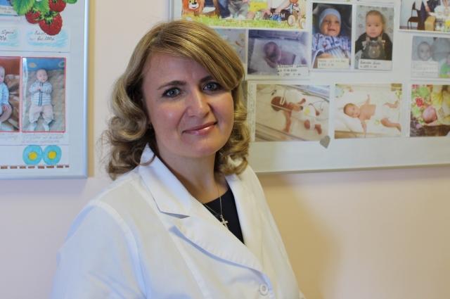 Ольга Лих на фоне фотографий малышей, родившихся в краевом перинатальном центре.