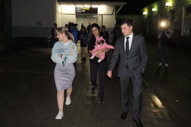 Кэрол Феннер с переводчицей и Андреем Алексуткиным идут из здания аэропорта к машине.
