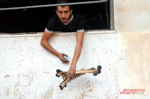 Сирийский солдат показывает найденные в доме человеческие кости