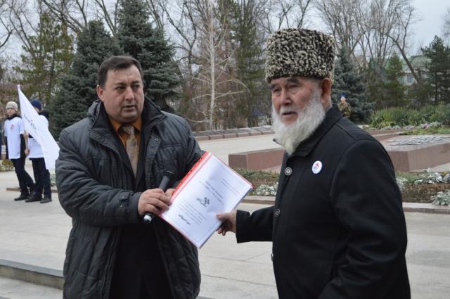Григорий Касмынин вручает документы отца имаму аула Бейсей Хасанби Эшееву.