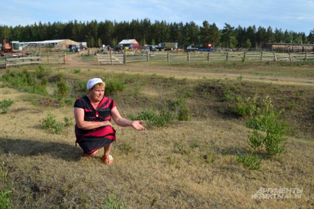 Управляющая фермой Татьяна Горковенко показывает, насколько поле выжжено солнцем