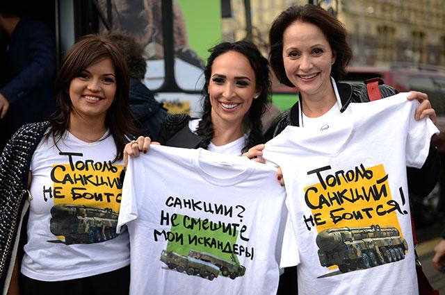 Президент фонда «Содействие» Ксения Мельникова, дизайнер футболок Анастасия Задорина и актриса Ольга Кабо (слева направо) демонстрируют футболки с патриотической символикой на Пушкинской площади в Москве.