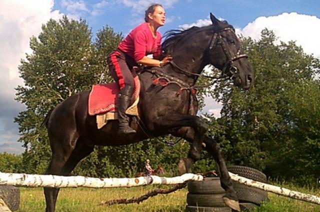 Конь с всадником с легкостью преодолевает барьеры.