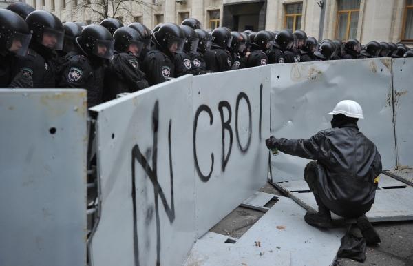 Протестующий пишет слово свобода на металлическом заграждении во время митинга сторонников евроинтеграции Украины в Киеве. 01.12.2013