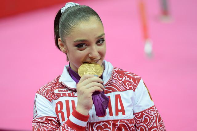 Россиянка Алия Мустафина, занявшая первое место в упражнениях на брусьях во время финальных соревнований по спортивной гимнастике среди женщин на ХХХ Олимпийских играх 2012 года в Лондоне, на церемонии награждения.