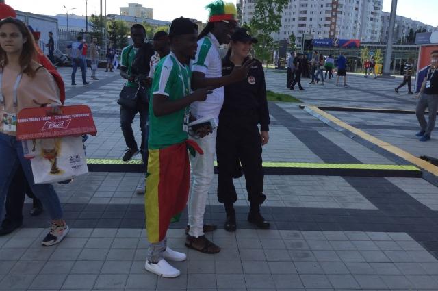 Футбол сближает: сенегальские болельщики и российская сотрудница полиции.