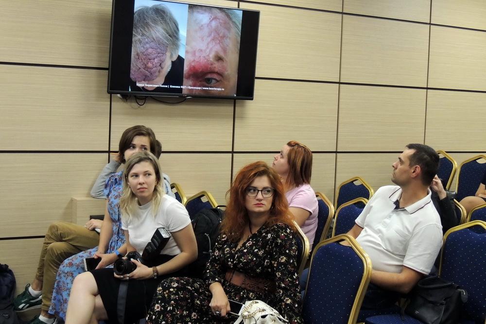 Журналисты смотрят фото пациента, которого вылечил Павел Попова.