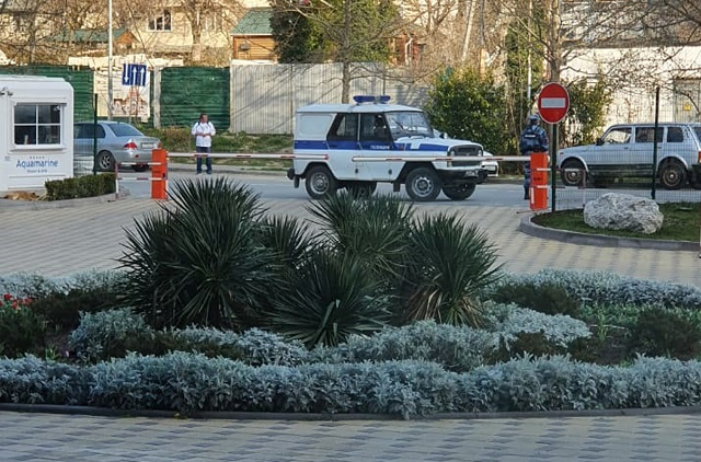 Полицейские дежурят у шлагбаума, чтобы постояльцы гостиницы не уехали.