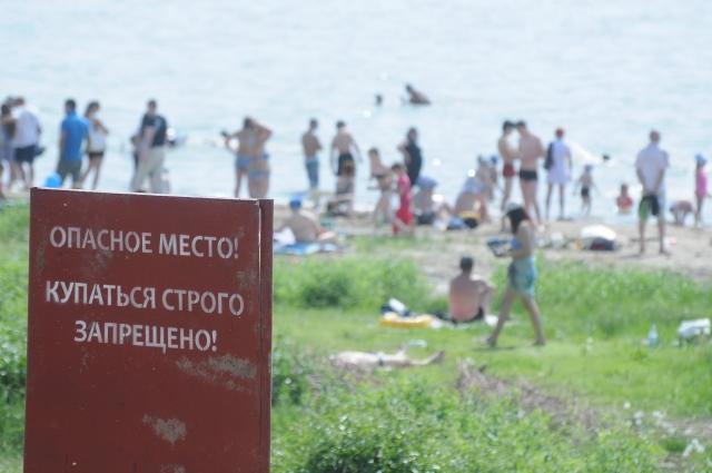 Люди купаются в реке несмотря на предупреждение.