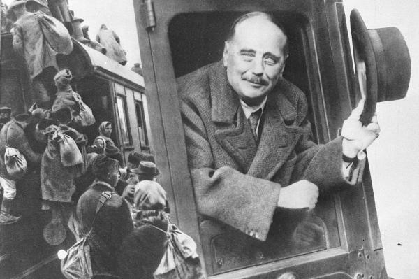 Английский писатель Герберт Уэллс смотрит из окна железнодорожного вагона. Репродукция фотографии.