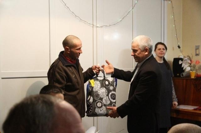 Основатель шелтера Виктор Кочнев вручает подарок бездомному.