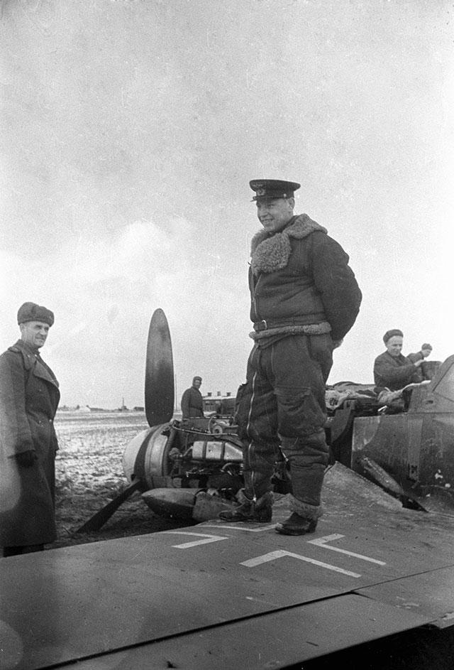Александр Покрышкин стоит на сбитом фашистском самолете, 1945 г.