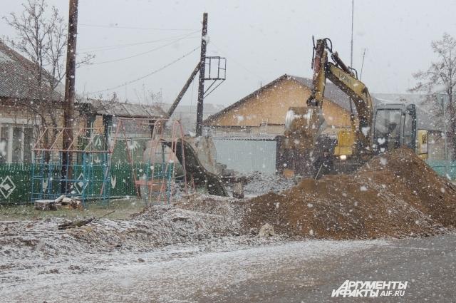 В селе выпал снег, люди греются обогревателями.