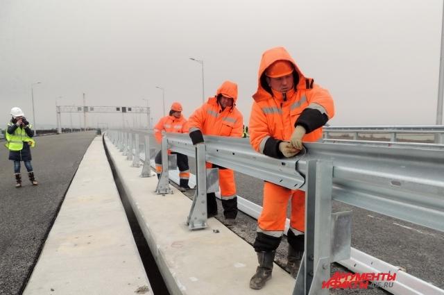 Строители монтируют отбойники на автомобильном мосту.