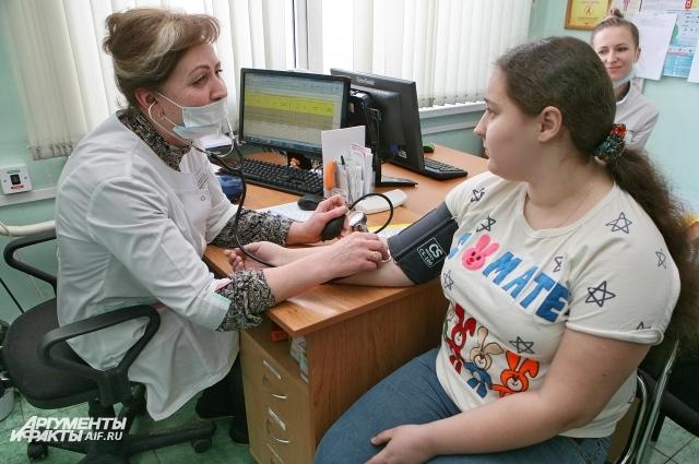 Фельдшер Наталья Павлюченко  измеряет давление пациентке.