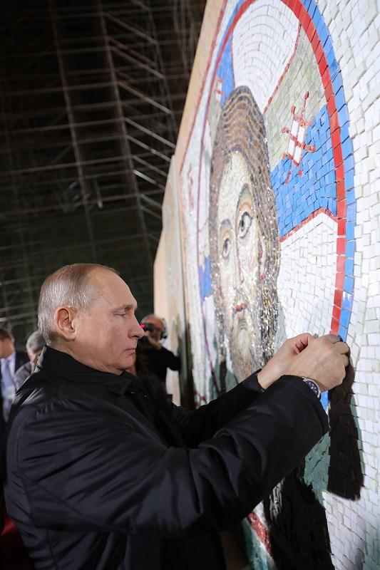 Владимир Путин укладывает фрагмент мозаики «Образ Нерукотворный» вхраме святого Саввы вБелграде.