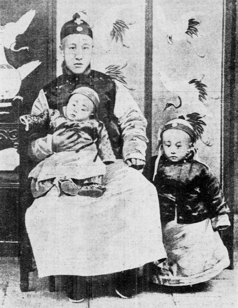 В 1908 году после убийства императора Куанг Ся (Гуан Сюй) на трон взошел трехлетний Пу И. На фото он стоит справа от своего отца, принца-регента Чуна, который держит на коленях младшего сына.