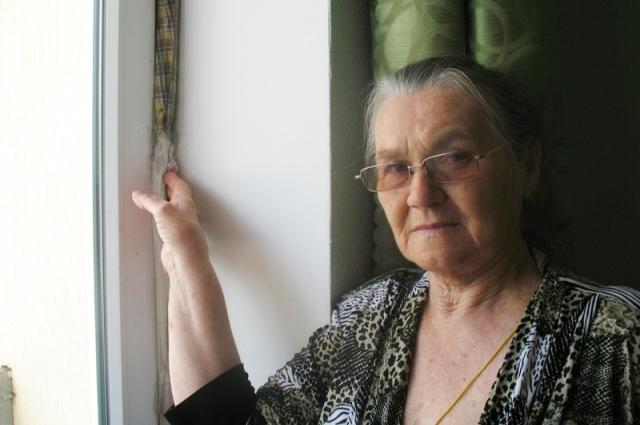 Анна Золотарёва затыкает щели полотенцами.
