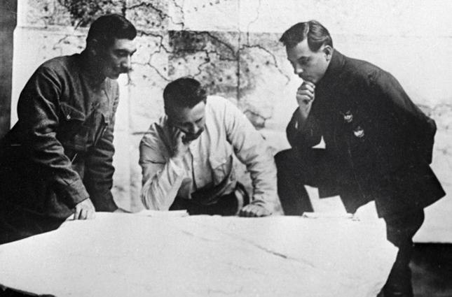 Михаил Васильевич Фрунзе (в центре), Семен Михайлович Буденный (слева) и Клим Ворошилов (справа) разрабатывают план разгрома Врангеля.
