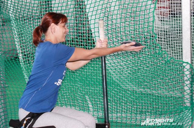 Елена тренируется сидя, ее парализованные ноги зафиксированы.