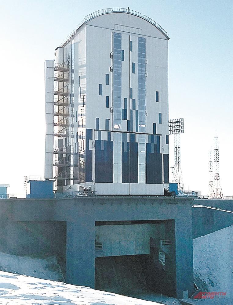 Над стартовым столом ракету уже ждёт мобильная башня обслуживания.