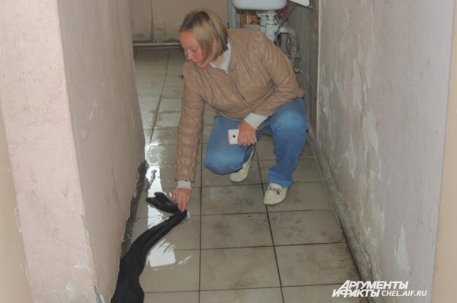Надежда Никоскина привычно вытирает туалетную воду около своей комнаты.