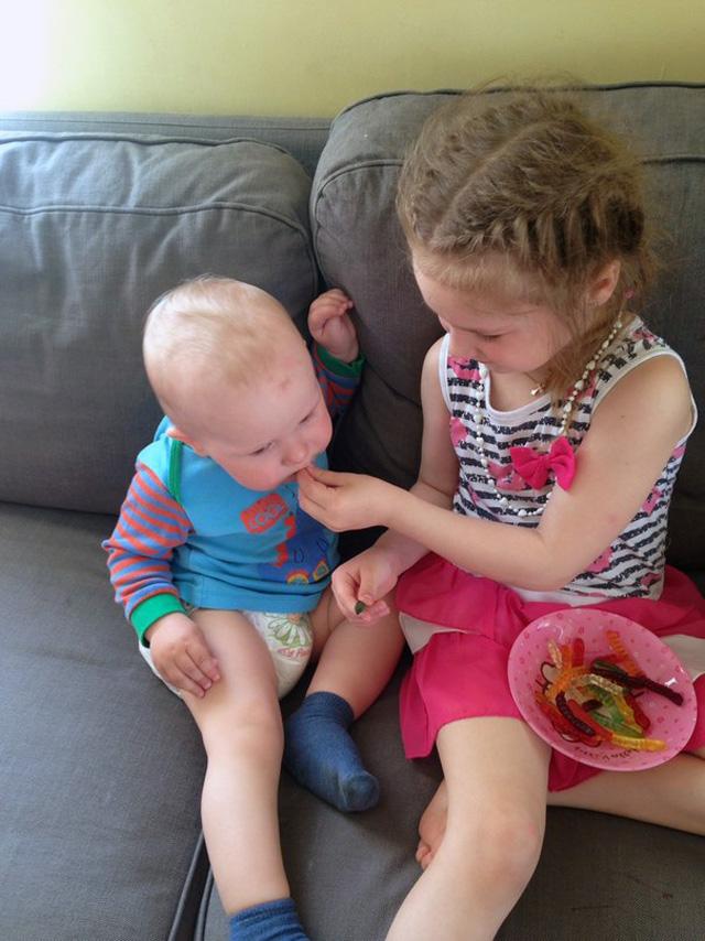 Старшая сестренка всегда накормит младшего братика.