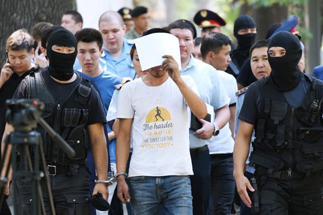 Полицейские и подозреваемый в убийстве фигуриста Дениса Тена Нуралы Киясов (в центре) на месте преступления в Алма-Ате.