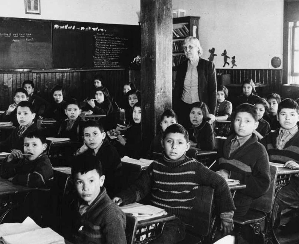 Ученики сидят в классе школы-интерната Всех Святых в Лак-ла-Ронге, Саскачеван, Канада, около 1950 года. Фотография сделана около 1950 года.