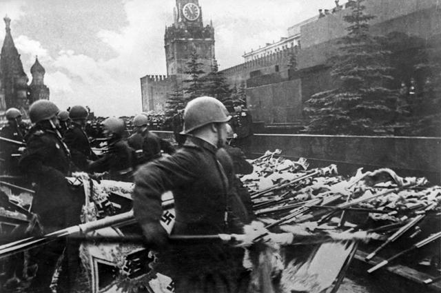 Участники парада бросают к подножию Мавзолея В. И. Ленина немецкие знамена.