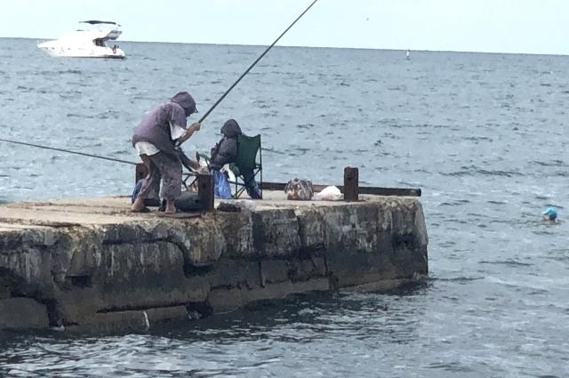 На волнорезах как всегда много рыбаков.