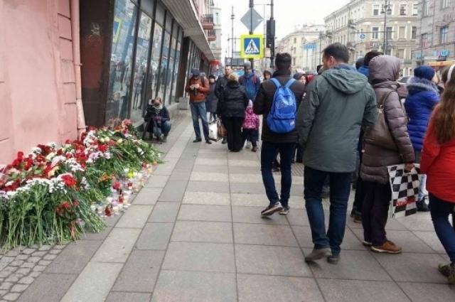 Люди несут цветы к месту трагедии.