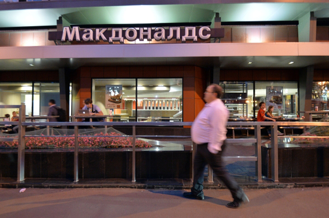 Мужчина проходит мимо закрытого ресторана быстрого питания