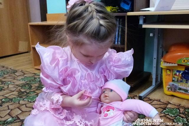 Малышка заботится о кукле.