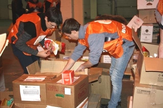 Волонтеры за сортировкой подарочных наборов.