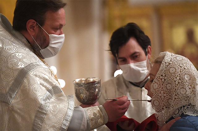 Священнослужитель причащает прихожанку в храме Христа Спасителя в Москве, открывшемся после карантина.